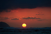 A big red ball of fire sits on the ocean horizon at Kaena Point on Oahu at sunset. Taken by Hawaii Photographer, Scott Sharick