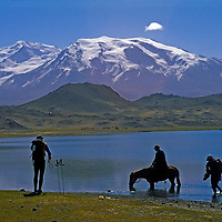 Foreign trekkers pass a Khyrgiz horseman beside Lake Karakul in the Pamir Mountains of far-western China. 7,546-meter [Mount] Mustagh Ata rises in the background.