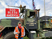 Adam Lange, founder of the grassroots group United Cape Patriots that supports President Trump, stands alongside his salvaged Army troop carrier. Lange joins dozens assembled at the Bourne Rotary on Cape Cod to peacefully protest the results of the 2020 presidential election.