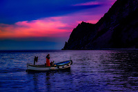 """""""Laying of fishing nets as the sun sets over the Gulf of Monterosso al Mare""""...<br /> <br /> I began my daily journey at the northern most town of Monterosso and took the train to the southernmost town of Riomaggiore. Upon arriving in this picturesque seaside village and moving down to the water's edge, I noticed proprietor Francesco in front of a tiny boat rental sign. After arranging an evening sail up the coast, I was able to focus on the colorful persona of Riomaggiore. That evening I sailed up the coast photographing each Cinque Terre town along the way aboard the Angelina Dada. Upon arriving back home in Monterosso, soft light illuminated the sky and azure sea of the Mediterranean convincing me to sail all the way back to Riomaggiore with my gracious guides Claudio and Eddie of """"Cinque Terre dal Mare"""" sailing excursions. We arrived just in time for a perfect sunset and a perfect evening for creating bellissimo new images. After a nice dinner...I caught the last train at midnight back home to Monterosso. A very long day, but worth every minute! When thinking of Italy, one does not ponder its massive coastline of 4,700 miles, all blessed with a great variety of meraviglioso gourmet of the sea.  The site of this fisherman is commonplace upon all the azzurro mare of Italy."""