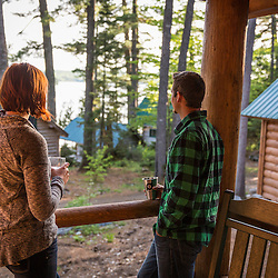 A young couple enjoy an evening on the porch of a cabin at the Appalachian Mountain Club's Gorman Chairback Lodge. Long Pond. Near Greenville, Maine.