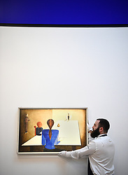 A gallery assistant adjusts Tischgesellschaft by Oskar Schlemmer during a photo call for Sotheby's Impressionist, Modern Art and Surrealist Art sales, in London.