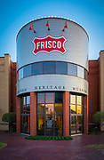 """Frisco Heritage Museum in Frisco, Texas. Frisco is a city in Collin and Denton counties in Texas. It is part of the Dallas-Fort Worth metroplex, and is approximately 25 miles from both Dallas Love Field and Dallas/Fort Worth International Airport. Since 2003, Frisco has received the designation """"Tree City USA"""" by the National Arbor Day Foundation. When the Dallas area was being settled by American pioneers, many of the settlers traveled by wagon trains along the old Shawnee Trail. This trail was also used for cattle drives north from Austin. This trail later became the Preston Trail, and later, Preston Road. Preston Road is one of the oldest north-south roads in all of Texas. With all of this activity, the community of Lebanon was founded along this trail and granted a U.S. post office in 1860. In 1902, a line of the St. Louis-San Francisco Railway was being built through the area, and periodic watering stops were needed along the route for the steam locomotives. The current settlement of Lebanon was on the Preston Ridge and was thus too high in elevation, so the watering stop was placed about four miles (6 km) to the west on lower ground. A community grew around this train stop. Residents of Lebanon actually moved their houses to the new community on logs. The new town was originally named Emerson, but the U.S. Postal Service rejected the name as being too similar to another town in Texas. In 1904, the residents chose Frisco City in honor of the St. Louis–San Francisco Railway on which the town was founded, later shortened to its present name."""