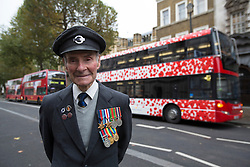 © licensed to London News Pictures. London, UK 26/10/2012. Ian Aitchison, 89, an ex-WWII soldier and ex-bus driver who worked for 35 years, posing next to a bus wrapped in the poppy design to highlight the Comrades' role in the Remembrance Sunday Parade and mark TfL's activities to raise awareness of the sacrifices made by London's service men and women. Photo credit: Tolga Akmen/LNP
