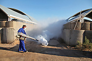 Iraqi worker spraying insect repellent on Coalition base on a daily basis