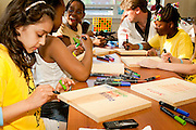 Children working on an art activity using markers to draw on wooden boards.