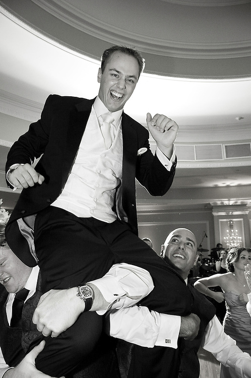 Black and White photo of Groom Carried on his friends' shoulders on dance floor at his Wedding