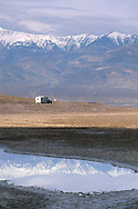 Towing 5th wheel travel trailer camper on road below Panamint mountains refelceted in pool of water,  near Badwater, Death Valley, California