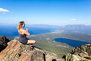 Woman meditates on a rock on mount Tallac overlooking lake Tahoe California