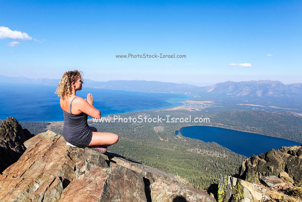 Woman meditates on a rock on mount Tallac overlooking lake Tahoe California