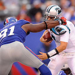 Quarterback Jimmy Clausen #2 of the Carolina Panthers eludes a sack attempt by Justin Tuck #91 of the New York Giants during second half NFL action in the New York Giants' 31-18 victory over the Carolina Panthers at New Meadowlands Stadium in East Rutherford, New Jersey.