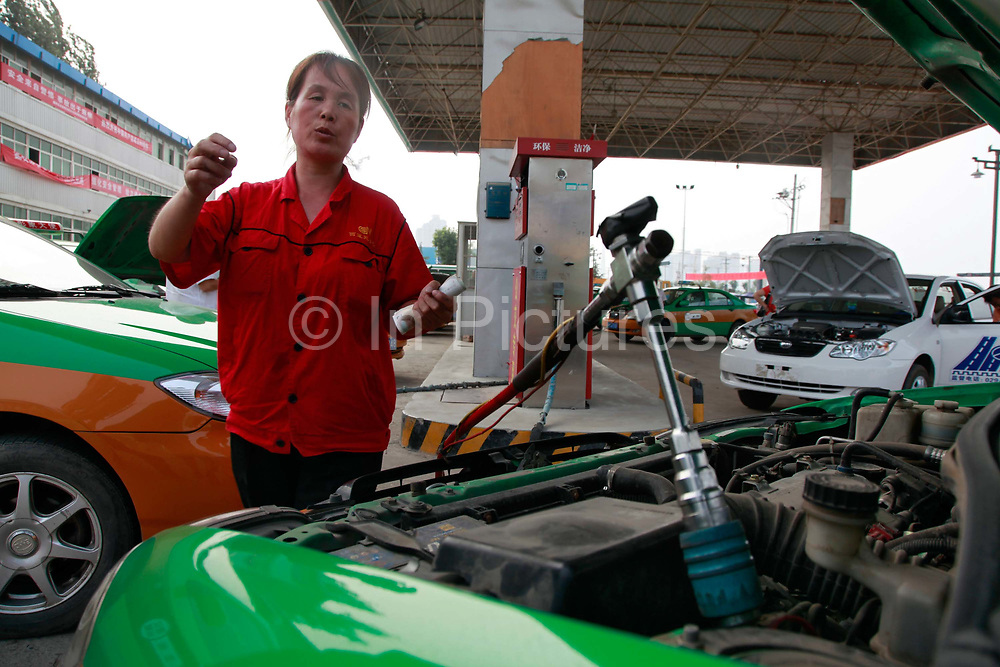 Taxi drivers wait to fill up their cars at a China Natural Gas filling station in Xi'an, Shaanxi Province,  China on 11 August 2011. Many city buses and taxis arounf the country are now using natural gas as a cheaper alternative to gasoline.