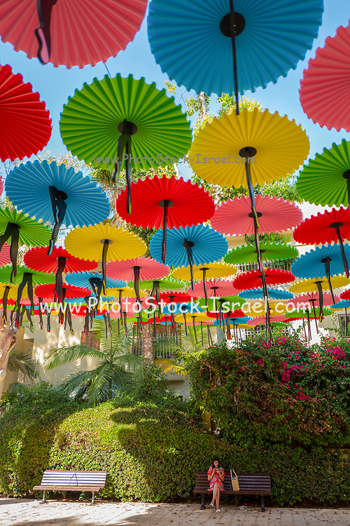Colourful parasols strung up together over a park on a blue sky background