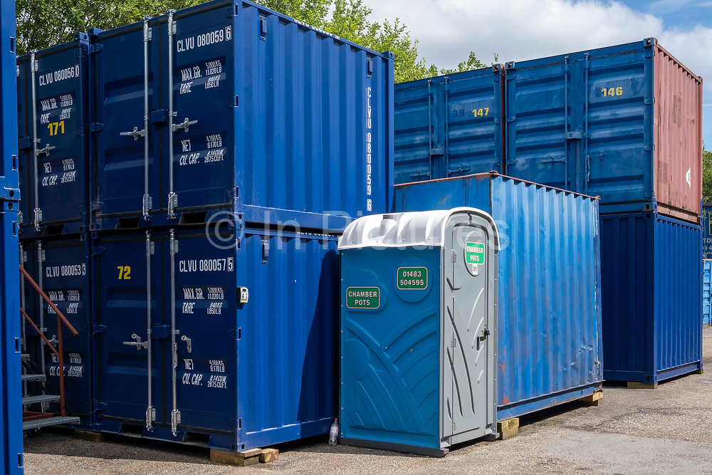 A portable toilet unit next to two rows of stacked blue metal storage shipping containers in a self-storage depot on 17th June 2019 in Aldershot, Hampshire, United Kingdom.