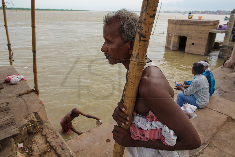Man resting after bathing at Dattatreya Ghat, by the Ganges river, in Varanasi, India.