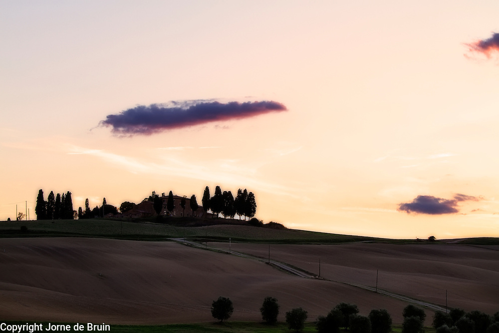 A house surrounded by trees on a Tuscan hill under a sunset sky
