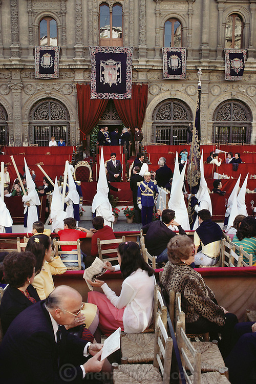 Hooded penitents in a procession during Holy week in Seville, Spain. Street processions are organized in most Spanish towns each evening, from Palm Sunday to Easter Sunday. People carry statues of saints on floats or wooden platforms, and an atmosphere of mourning can seem quite oppressive to onlookers.