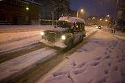A brave taxi cab driver drives gingerly along Denmark Hill in South London, The capital's infrastructure has largely come to a halt due to the large amounts of snowfall that has hit the capital - the most for 18 years. In addition to the lack of buses, trains were severely affected and roads like this have not been gritted by the local borough council, leaving motorists struggling to control their vehicles is the slippery conditions. The taxi's orange light is still illuminated indicating he is free for hire and a foot of snow is piled on his roof as the headlights pick out the driving blizzard conditions. Footprints are already in the drift near the pavement that is now hidden from the road.