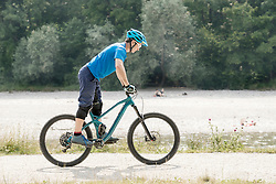 Man riding with mountain bicycle while standing on pedals along river, Bavaria, Germany