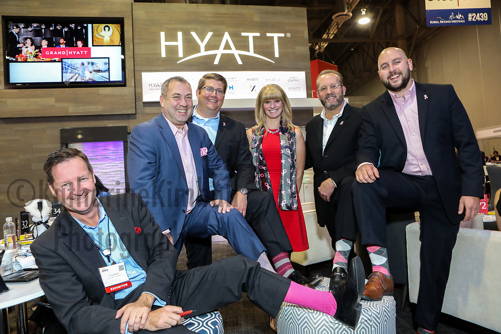 Members of the Hyatt Hotels Corporation booth at IMEX America Expo show off their pink in support of fighting breast cancer.