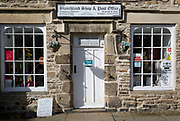 Closed for the Saturday afternoon is the local shop and post office in the Northumbrian village of Blanchland, on 29th September 2017, in Blanchland, Northumberland, England. Blanchland is a village in Northumberland, England, on the County Durham boundary. The population of the Civil Parish at the 2011 census was 135. Blanchland was formed out of the medieval Blanchland Abbey property by Nathaniel Crew, 3rd Baron Crew, the Bishop of Durham, 1674-1722. It is a conservation village, largely built of stone from the remains of the 12th-century Abbey. It features picturesque houses, set against a backdrop of deep woods and open moors. Set beside the river in a wooded section of the Derwent valley, Blanchland is an attractive small village in the North Pennines Area of Outstanding Natural Beauty.