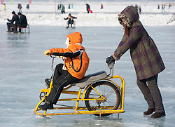 Children playing with ice bicycle on the frozen Songhua River in Harbin China during winter 2009