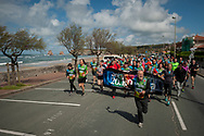 """Runners on the 20th Korrika pass by Hondarraitz beach.  Hendaia (Basque Country). April 4, 2017. The """"Korrika"""" is a relay course, with a wooden baton that passes from hand to hand without interruption, organised every two years in a bid to promote the basque language. The Korrika runs over 11 days and 10 nights, crossing many Basque villages and cities. This year was the 20th edition and run more than 2500 Kilometres. Some people consider it an honour to carry the baton with the symbol of the Basques, """"buying"""" kilometres to support Basque language teaching. (Gari Garaialde / Bostok Photo)"""