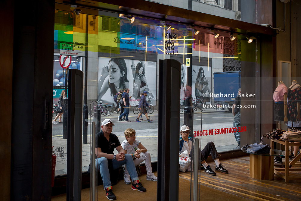 Shoppers wait at the entrance of Urban Outfitters, on 31st July 2017, in Oxford Street, London, England.