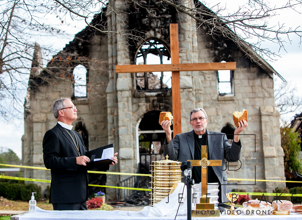 The Rev. D. Brent Nichols, pastor of St. Paul Lutheran church in Pomaria, breaks bread for communion during a Sunday morning service in front of the church. The church was heavily damaged in a fire Thursday morning. At left is The Rev. Dr. Herman R. Yoos III, Bishop of the South Carolina Synod. Photo by Columbia, SC, photojournalist Jeff Blake