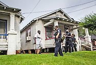 Man walking back to his house in Baton Rogue police stand on the lawn of  home  in Baton Rouge on Sunday, July 10, 2016.  6 days following the Alton Sterling shooting, the police areseted Aproximaetly 48 people had been were taken into custody by midnight Sunday,