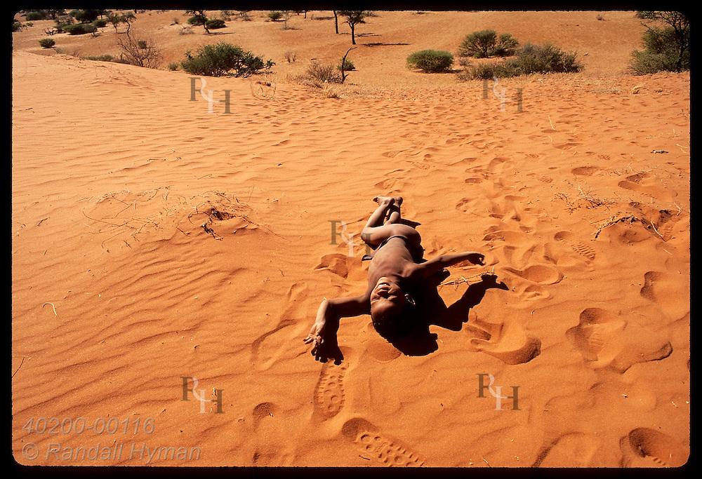 Bushmen boy rolls in sand surrounded by Western footprints on a red Kalahari dune; Intu Afrika. Namibia