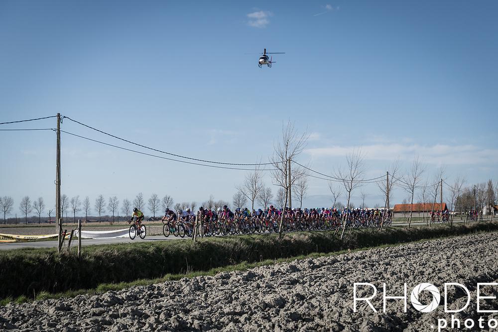 Peloton rolling through De Moeren<br /> <br /> Oxyclean Classic Brugge-De Panne 2021 (WE/1.WWT) - Belgium<br /> 1 day race from Brugge to De Panne (159km)<br /> <br /> ©RhodePhoto