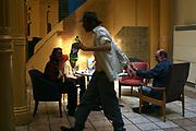 Men sitting around in a wet house hostel drinking cider, London.