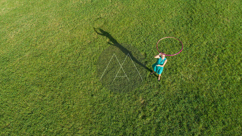 Aerial view of a woman playing with Hola Hoop at Tudmana Park, a public park in Zagreb downtown, Croatia.