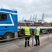 Nederland Zuid-Holland Rotterdam  27-08-2009 20090827 Foto: David Rozing .Serie over logistieke sector.ECT Delta terminal in de haven van Rotterdam. Vrachtwagen chaufeurs maken een praatje terwijl zij wachten op de vracht. Telescopische spreader voertuigen vervoeren de containers op de terminal  naar de vrachtwagens voor verder transport.  .ECT,European Container Terminals, at the Port of Rotterdam. Truck drivers waiting waiting for goods. Europe's biggest and most advanced container terminal operator, handling close to three- quarters of all containers passing through the Port of Rotterdam. ECT is a member of the Hutchison Port Holdings group (HPH), the world biggest container stevedore with terminals on every Continent. At the ECT Delta Terminal telescopic spreader vehicles transport the containers between ship and stack / trucks.  Terminal operations are highly automated for discharging and loading large volumes , vrachtwagenchauffeur, vrachtwagenchauffeurs, wachten, wachttijd, wachttijden, wagen, wagens, waiting, weinig voldoening, werk, werkzaamheden, working class, zonder inhoud..Holland, The Netherlands, dutch, Pays Bas, Europe .Foto: David Rozing