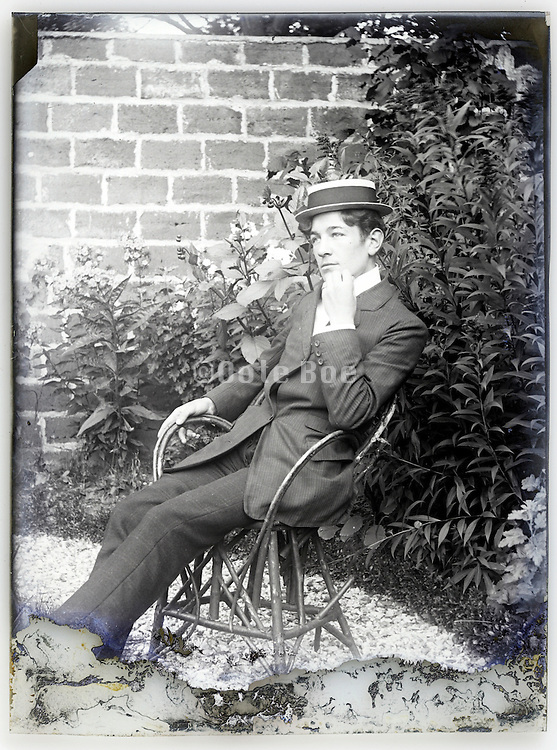 old deteriorating glass plate with young well dressed man sitting in backyard