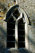 Norman style old stone window at 11th Century St Nicholas Church, Oddington, near Stow on the Wold, Gloucestershire