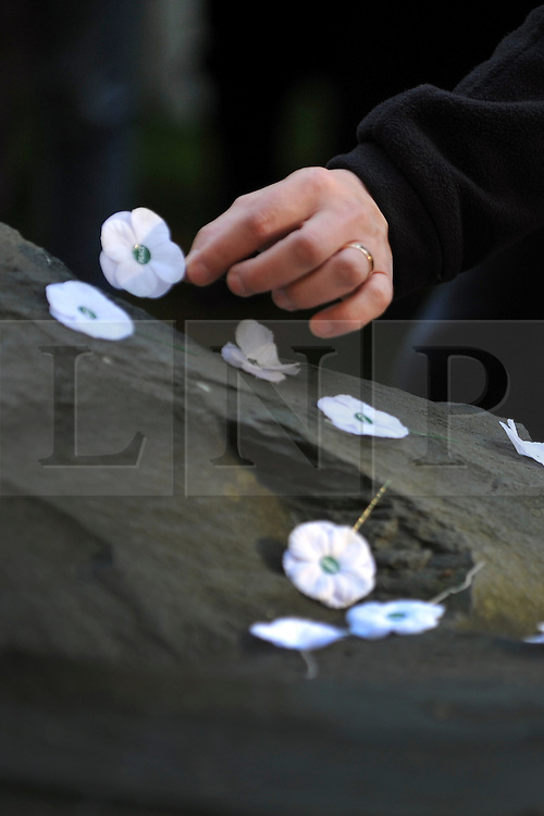 © Licensed to London News Pictures. 13/11/2011. London, UK. People place white poppies  on the memorial at the service.  Pledge Union White Poppy Remembrance Ceremony at the Conscientious Objectors Memorial in Tavistock Square Gardens today,  Sunday 13th Nov. Photo credit : Stephen Simpson/LNP