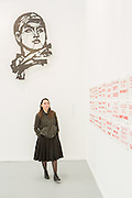 """New York, NY - 6 May 2016. Frieze New York art fair. A visitor takes in the exhibits in the Marian Goodman Gallery, which has outlets in New York, London and Paris. The piece with the red text is Wiliam Kentridge's """"In Mockery of Progress."""""""