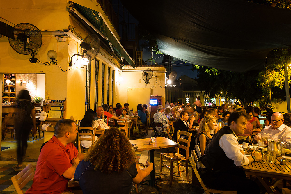 People are seen hanging out at Suzanna Cafe and Restaurant in Tel Aviv's Neve Tzedek neighborhood