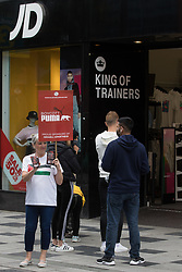 Slough, UK. 10th July, 2021. A pro-Palestinian activist canvasses support from the public outside a branch of JD Sports during a Boycott Puma day of action. The nationwide day of action was organised by Palestine Solidarity Campaign in protest against Puma's sponsorship of the Israeli Football Association, which includes clubs playing in Israeli settlements in the occupied West Bank, and in response to a call from Palestinians to mark the 16th birthday this week of the Boycott, Divestment and Sanctions (BDS) movement.