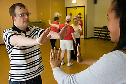 Boyfriend and girlfriend day service users with learning disabilities doing a dance move,