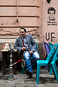 A man smokes a shisha pipe, at the Zahrat al-Bustan cafe, Cairo, Egypt