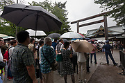 People line up in the rain to pay their respects to the war dead as Yasukuni shrine marks the 72nd anniversary of the end of the Pacific War. Yasukuni Shrine, Kudanshita, Tokyo Japan. Tuesday August 15th 2017. Nominally a event to honour Japan's war dead and call for continued peace, this annual gathering  at Tokyo's controversial Yasukuni  Shine also allows many Japanese nationalists to display their nostalgia for their Imperial past.Rightwing paramilitary groups, Imperial cos-players, politicians and many ordinary citizens come together at the shrine to march and wave flags. The day goes almost unreported in the mainstream Japanese media.