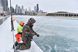© Licensed to London News Pictures. 31/12/2017. CHICAGO, USA.  Men take part in ice fishing off Navy Pier. The waters of Lake Michigan around Chicago have frozen during a period of sub-zero temperatures.  Extremely cold conditions are forecast to continue into the New Year. Photo credit: Stephen Chung/LNP