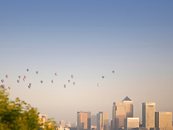 © Licensed to London News Pictures. 07/06/2015. London, UK. Hot air balloons rise over the London skyline on a summer morning. 50 Balloons took to the skies as part of the Lord Mayor's Regatta to raise money for charity. the last mass ascent balloon flight over London was over 20 years ago.Photo credit : Stu Mayhew/LNP