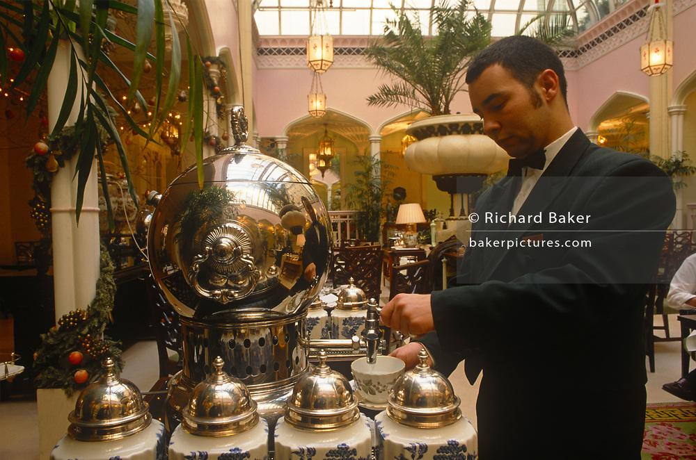 A waiter pours hot water from a silver urn for tea during an afternoon tea dance at the Waldorf Hotel's Palm Court, Waldorf Hilton Hotel, Aldwych., on 16th March 1997, in London, England.