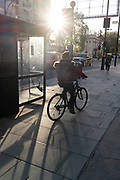 As the UK reacts to Prime Minister Boris Johnson's announcement of Lockdown 2 during the second wave of the Coronavirus pandemic, a cylist rides a bike through sunlight in Oxford Street, on 2nd November 2020, in London, England. From midnight on Thursday, all non-essential shops, bars, restaurants and other small businesses will have to closed, according to government Covid restrictions - and for a minimum of 4 weeks in the run-up to Christmas.