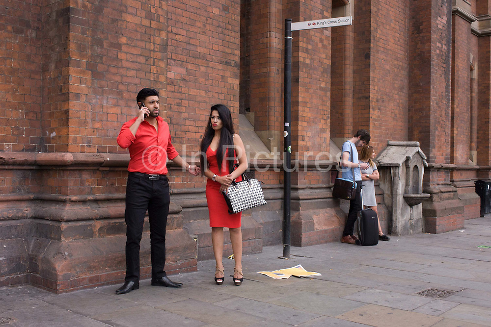 An Asian couple dressed in matching red, outside St. Pancras station, London. In conversation on the phone, he makes arrangements while his girlfriend stands awkwardly, over-dressed for this part of north London. At her feet is some newspaper blowing along the street.
