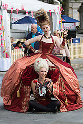 Trafalgar Square, London, June 12th 2016. Rain greets Londoners and visitors to the capital's Trafalgar Square as the Mayor hosts a Patron's Lunch in celebration of The Queen's 90th birthday. PICTURED: Two women in period costume pose for photographs.